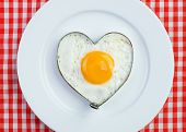 stock photo of yolk  - Fried egg in heart shape on vintage tablecloth - JPG