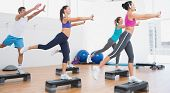 picture of step aerobics  - Female instructor with fitness class performing step aerobics exercise in gym - JPG