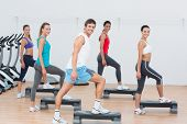pic of step aerobics  - Full length of instructor with fitness class performing step aerobics exercise in gym - JPG