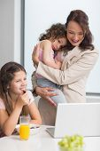 image of half-dressed  - Well dressed mother with daughters and laptop in the kitchen at home - JPG