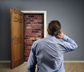 picture of scratching head  - Brick wall blocking the office doorway for a businessman concept for conquering adversity - JPG