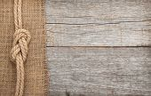 stock photo of ship  - Ship rope on old wood and burlap texture background with copy space - JPG