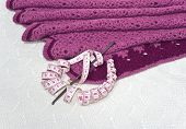 stock photo of knitwear  - Pink knitwear centimeter and a crochet hook are on the background of white openwork knitted fabric - JPG