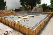 stock photo of reinforcing  - A house foundation site with steel reinforcement cages surrounded by wooden shuttering The cages are in the process of being laid out before the concrete is poured - JPG
