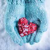 Female hands in light teal knitted mittens with entwined red heart on a white snow background. Love