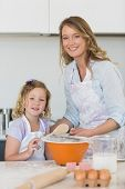 stock photo of flour sifter  - Portrait of mother and daughter making cookies at kitchen counter - JPG