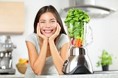 foto of vegan  - Green smoothie woman making vegetable smoothies with blender - JPG