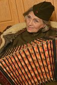 image of accordion  - Cute elderly woman solder playing accordion closeup - JPG