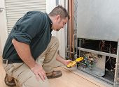stock photo of hvac  - HVAC technician using a meter to check heat pump amperage - JPG