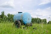 picture of cistern  - Blue water cistern for animal stand between pasture high grass and clovers move in wind - JPG