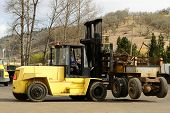 picture of junk-yard  - Large lift truck moving a old industrial steel trailer at a metal recycling scrap yard - JPG