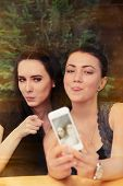 picture of two women taking cell phone  - Two girls taking a funny photo together with their smart phone - JPG