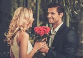 foto of bunch roses  - Handsome man with bunch of red roses dating his lady - JPG
