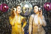 picture of catsuit  - two beautiful sexy disco women in gold and silver catsuits dancing in a club setting - JPG