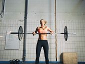 stock photo of snatch  - Young strong woman practices cross fit in a gym - JPG