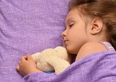 stock photo of child missing  - Cute little girl sleeping with a toy in her bed