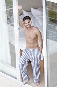 stock photo of partially nude  - Full length portrait of handsome young man standing at balcony doorway - JPG