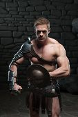 stock photo of sparta  - Half length portrait of young attractive warrior gladiator with muscular body posing with shield and sword on dark background - JPG