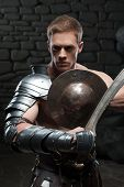 picture of sparta  - Half length portrait of young attractive warrior gladiator with muscular body posing with shield and sword on dark background - JPG