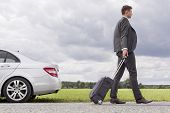pic of leaving  - Full length side view of young businessman with luggage leaving broken down car at countryside - JPG
