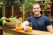 stock photo of restaurant  - Young fitted man enjoying an organic juice and vegetable in a raw restaurant - JPG