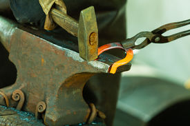 foto of blacksmith shop  - Making decorative element in the smithy on the anvil - JPG