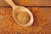foto of mustard seeds  - Mustard powder in wooden spoon on mustard seeds - JPG