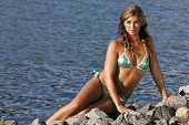 pic of swimsuit model  - A brunette bikini model posing outdoors against a body of water - JPG