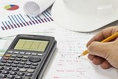 image of structural engineering  - Civil Design Engineer is making structural analysis calculations using a scientific calculator - JPG
