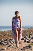 image of minx  - Happy young woman with dreadlocks walking along the seashore - JPG