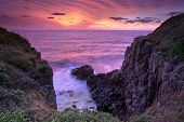 image of fiery  - Fiery red and orange sunrise skies bath the ocean and Minamurra volcanic landscape cliffs in beautiful rich and vibrant colours - JPG
