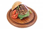 stock photo of hamburger  - extra thick hot beef meat hamburger dinner on wooden plate with tomatoes and salad isolated on white background - JPG