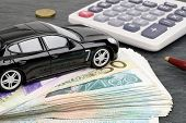 foto of luxury cars  - A luxury car sits on a stack on kroner notes with a calculator in the background - JPG