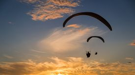 stock photo of glider  - 2 para gliders sail over the Pacific Ocean into a beautiful sunset - JPG
