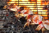 picture of bbq party  - Skewered Big Shrimps On The Hot BBQ Grill Flames of Fire In The Background - JPG