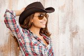 picture of cowgirls  - Beautiful young cowgirl adjusting her hat and smiling while standing against the wooden background - JPG