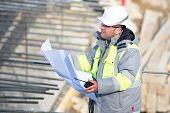pic of inspection  - Civil Engineer at at construction site is inspecting ongoing production according to design drawings - JPG