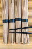 picture of bundle  - bundles of buckwheat soba noodles and black chopsticks on bamboo background - JPG