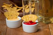 pic of nachos  - Mexican nacho chips cheese and salsa dip in bowl and tequila on wooden background