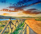 picture of shoreline  - colorful sunset by Porto Ferro shoreline - JPG
