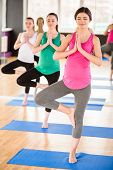 foto of pregnancy exercises  - Beautiful pregnant women in yoga class standing in a fitness studio doing exercise - JPG