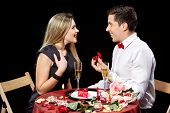 image of marriage proposal  - Man proposing marriage to a surprised woman on black background - JPG