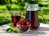 image of cherry  - cherry juice in a glass and carafe with cherries on natural background - JPG