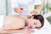 pic of ear candle  - Relaxed brunette getting an ear candling treatment at the spa - JPG