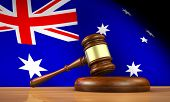 stock photo of justice law  - Australian law and justice concept with a 3d rendering of a gavel on a wooden desktop and the flag of Australia on background - JPG