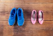 picture of pink shoes  - Running shoes and pink court shoes on a wooden floor background - JPG