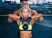 picture of kettles  - Woman workout with kettle ball and coach in gym - JPG