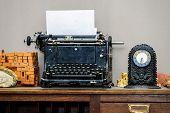 image of old vintage typewriter  - Old vintage typewriter with blank paper sheet in retro interior - JPG
