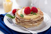 stock photo of curd  - Stack of pancakes with homemade lime curd and fresh raspberries - JPG