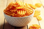 picture of potato chips  - Delicious potato chips in bowl on wooden table close - JPG